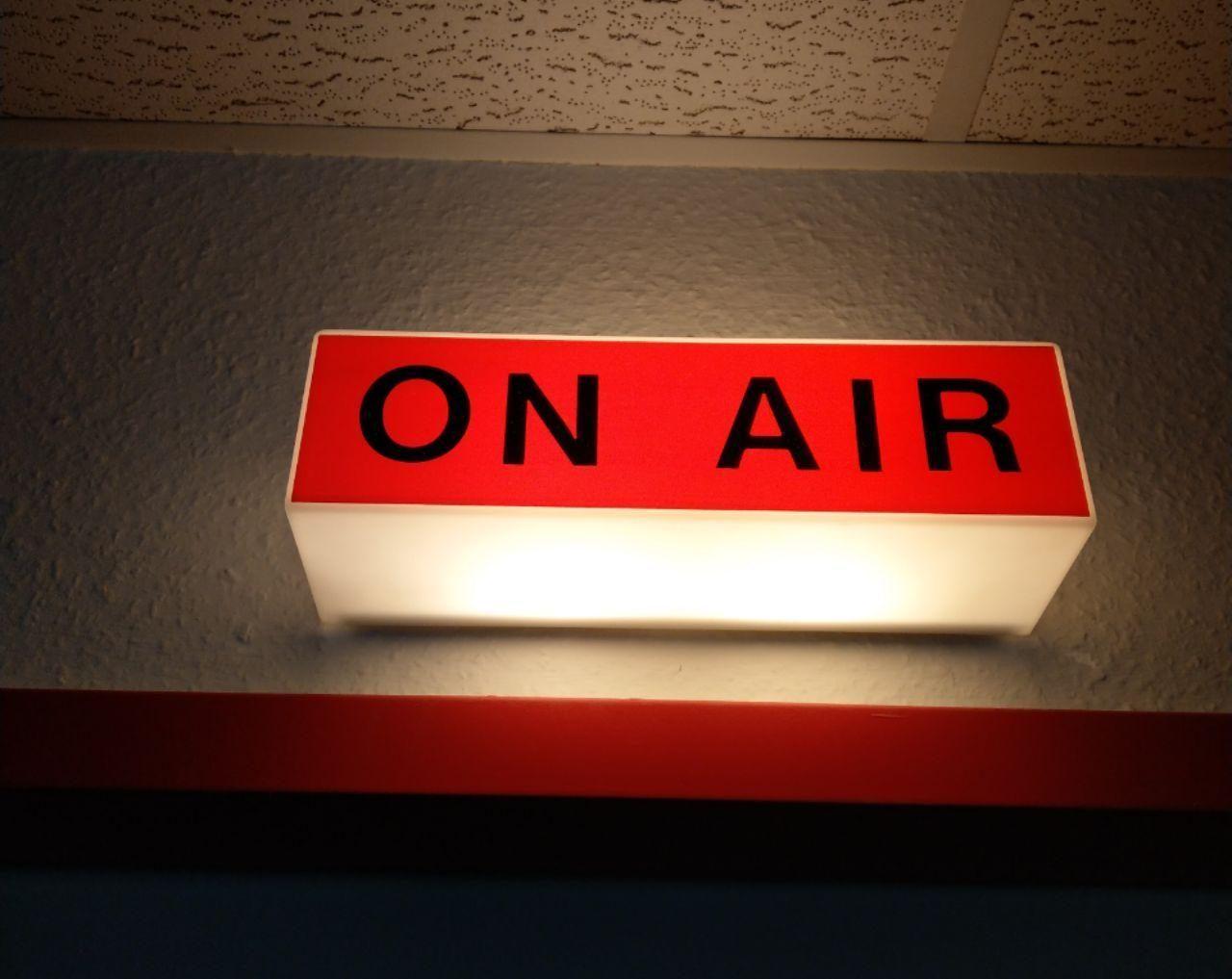 Das On-Air-Schild über der Studiotür leuchtet rot auf.