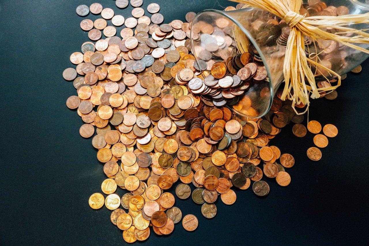 Auf dem Foto ist ein ausgekipptes Glas mit Münzen zu sehen.