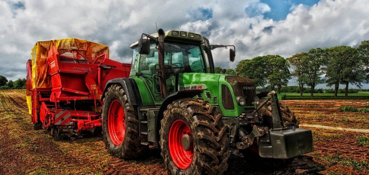 Auf dem Foto ist ein Traktor mit Anhänger auf einem Acker zu sehen.