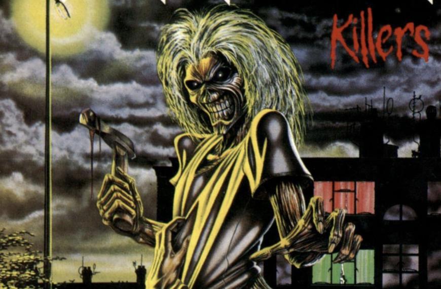 """Das Albumcover """"Killers"""" von Iron Maiden ist eine Zeichnung eines Menschen mit gruseliger Fratze, langen gelben Haaren und einer Axt in der Hand. Von unten ziehen Hände an dem Oberteil. Im Hintergrund sieht man die Silhouetten von Häusern, deren Fenster beleuchtet sind. Der Himmel ist dunkel."""