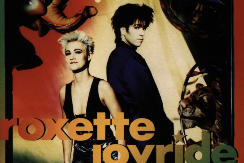 """Auf dem Albumcover """"Joyride"""" von Roxette sind Marie Fredriksson und Per Gessle zu sehen. Der Hintergrund ist sehr bunt und es sind eine Lichterkette, ein Elefant und ein Tiger zu sehen."""