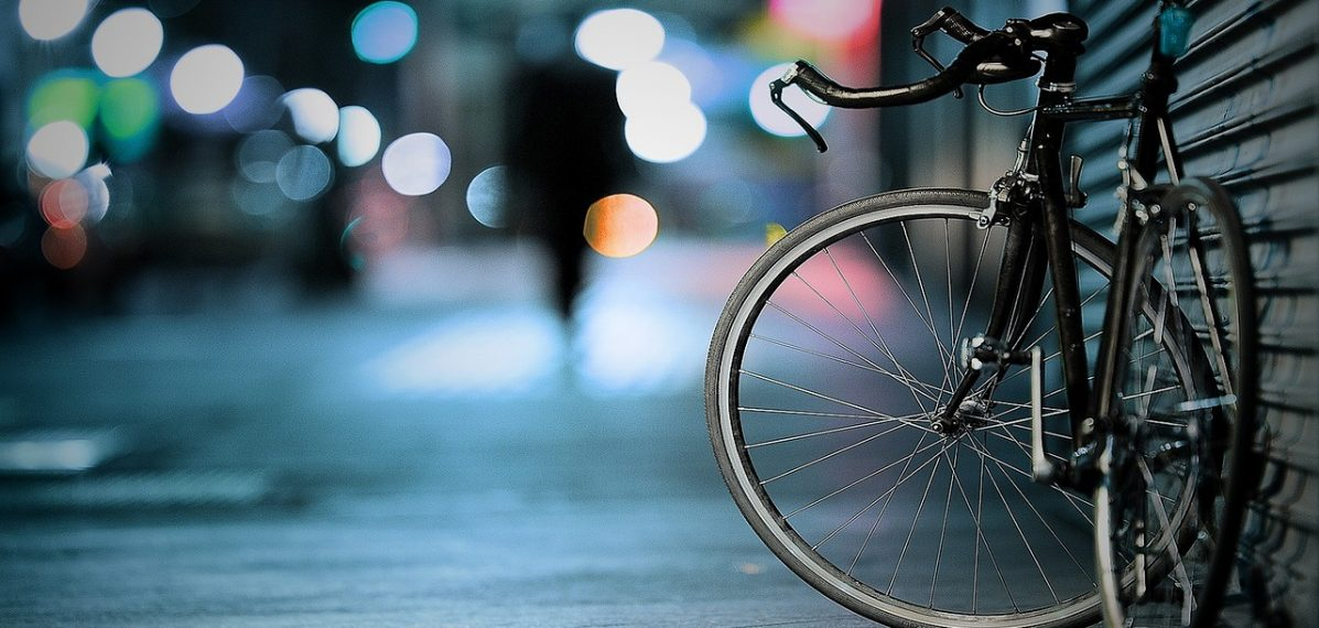 Auf dem Foto ist ein an der Wand abgestelltes Fahrrad vor einem unscharfen Hintergrund zu sehen.