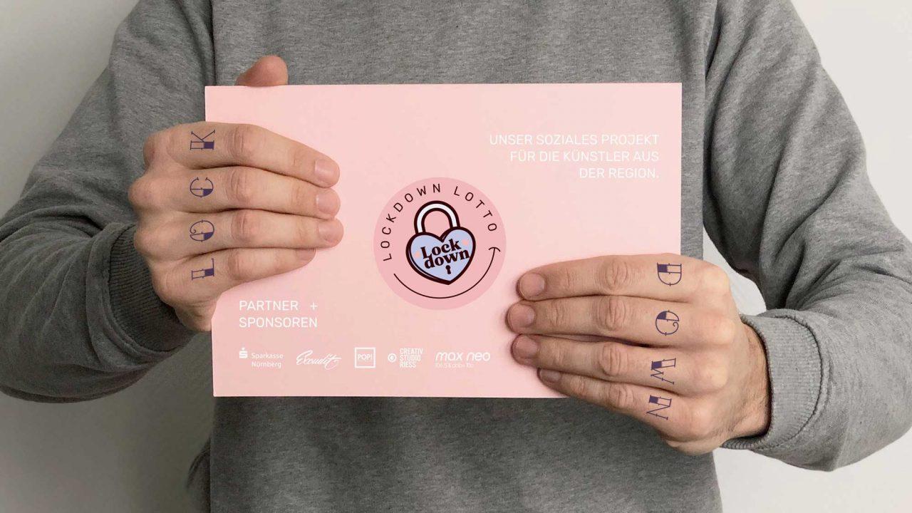 Auf dem Foto ist ein Mensch zu sehen, der ein Zettel in der Hand hält, auf dem das Logo vom Lockdown Lotto sowie von den verschiedenen Partner und Sponsoren abgebildet sind.