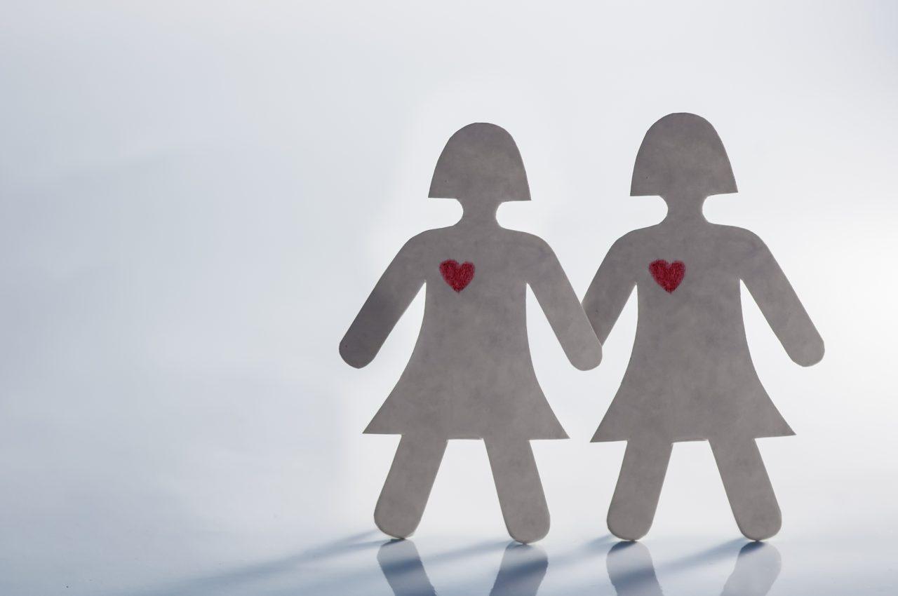 Auf dem Foto sieht man zwei Frauen aus Papier, die Händchen halten.