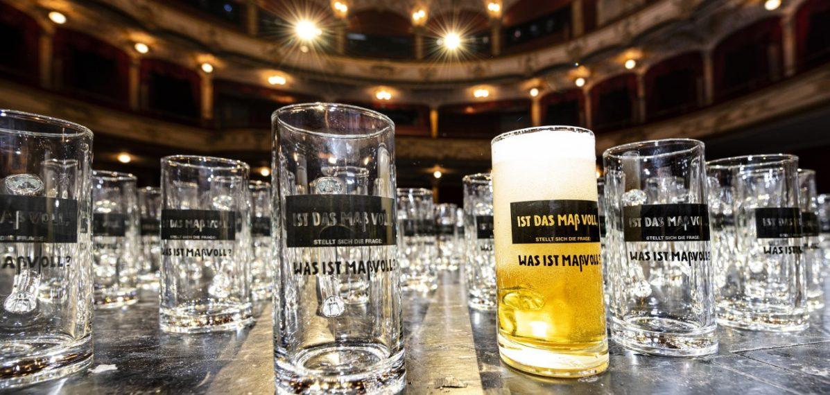 Auf dem Foto sieht man ein volles und zahlreiche Bierkrüge, die auf der Bühne des Fürther Stadttheaters stehen.
