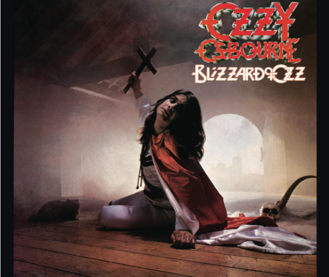 """Auf dem Albumcover """"Blizzard Of Ozz"""" von Ozzy Osbourne ist der Musiker zu sehen. Er sitzt auf einem Holzboden, um ihn herum wabert Nebel und man sieht eine Holzdecke. Osbourne hält drohend ein Kreuz in der Hand."""