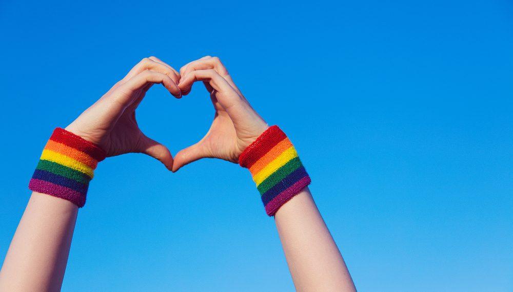 Man sieht zwei Hände, die ein Herz vor einem blauen Himmel bilden. An den Handgelenken befinden sich Schweißbänder in Regenbogenfarben.