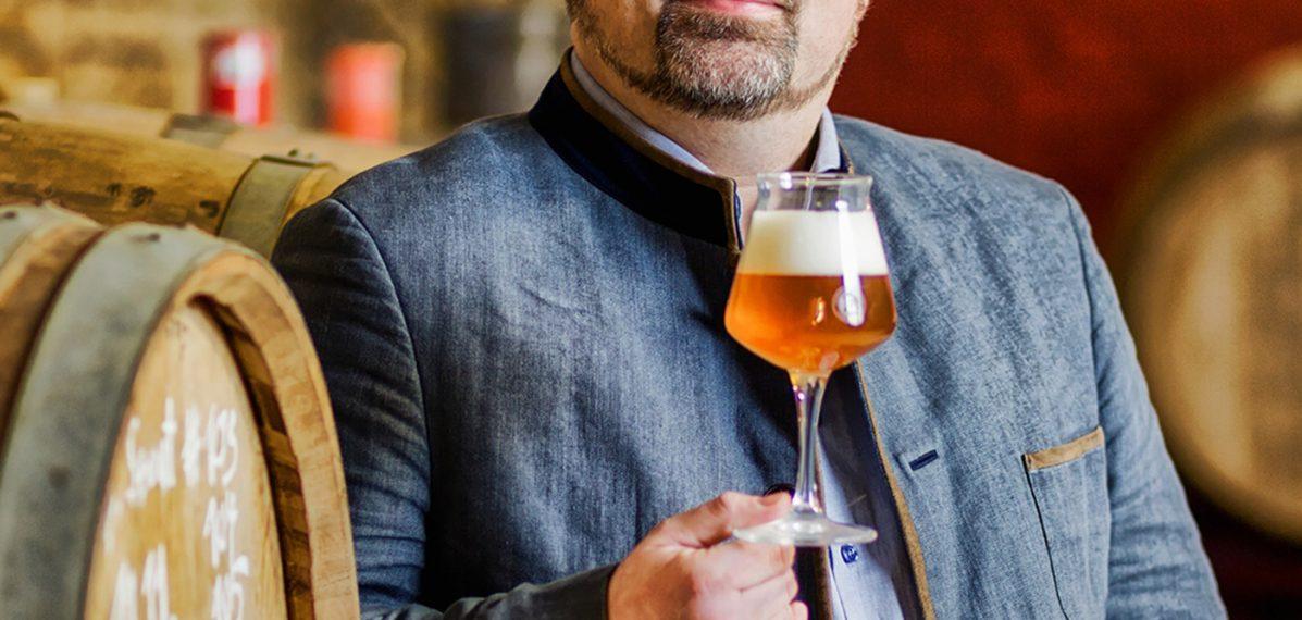 Auf dem Foto ist Markus Raupach mit einem Bier in der Hand vor Bierfässern zu sehen.