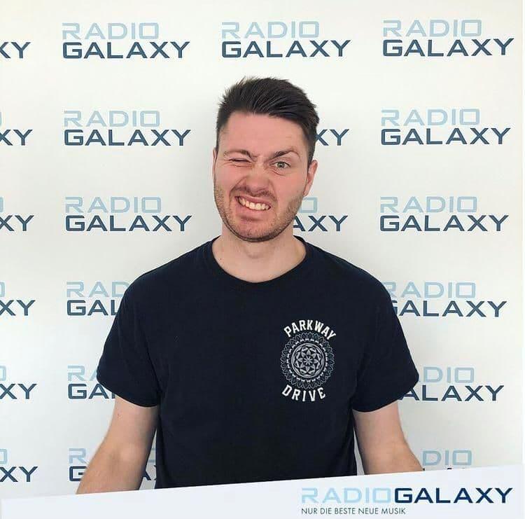 """Felix Körting steht vor einer Werbewand, auf der """"Radio Galaxy"""" steht."""