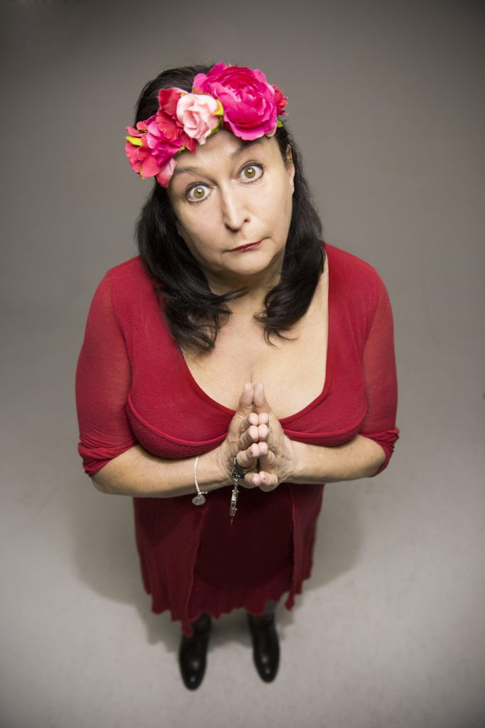 Lizzy Aumeier hat einen Blumenkranz auf dem Kopf und trägt ein rotes Kleid. Sie wurde von oben fotografiert.