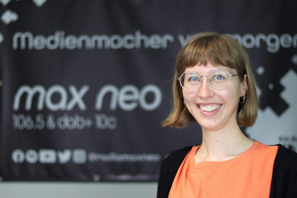 Unsere Praktikantin Maria Czerniejewski im Porträt vor dem max neo Banner.
