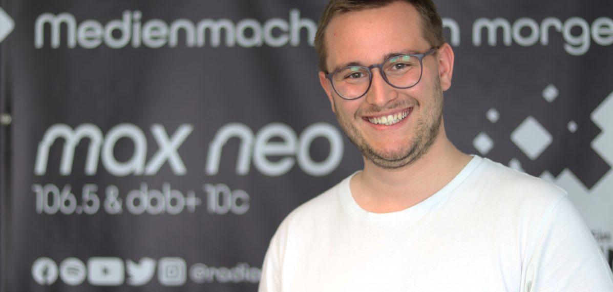 Sven Stefani steht vor einem max neo Banner.