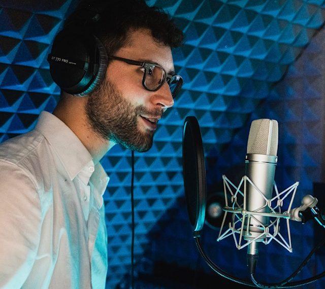 Yves Simon spricht in seinem Homestudio in ein Mikrofon.