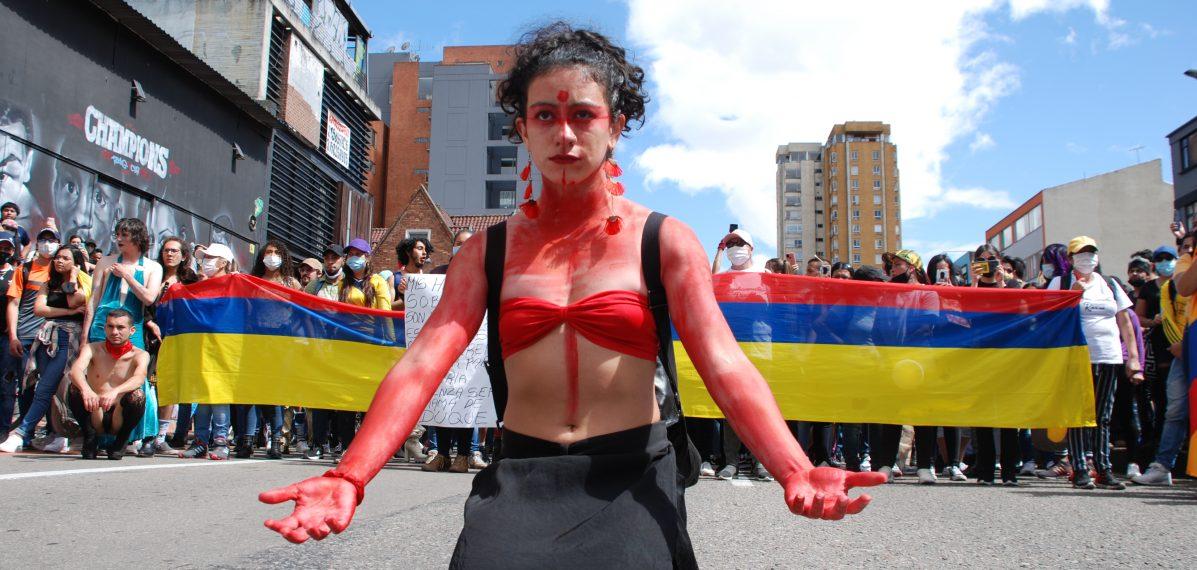 Eine Frau ist rot bemalt und kniet auf der Straße, im Hintergrund stehen Menschen in einer Reihe und halten eine kolumbianische Flagge in der Hand.