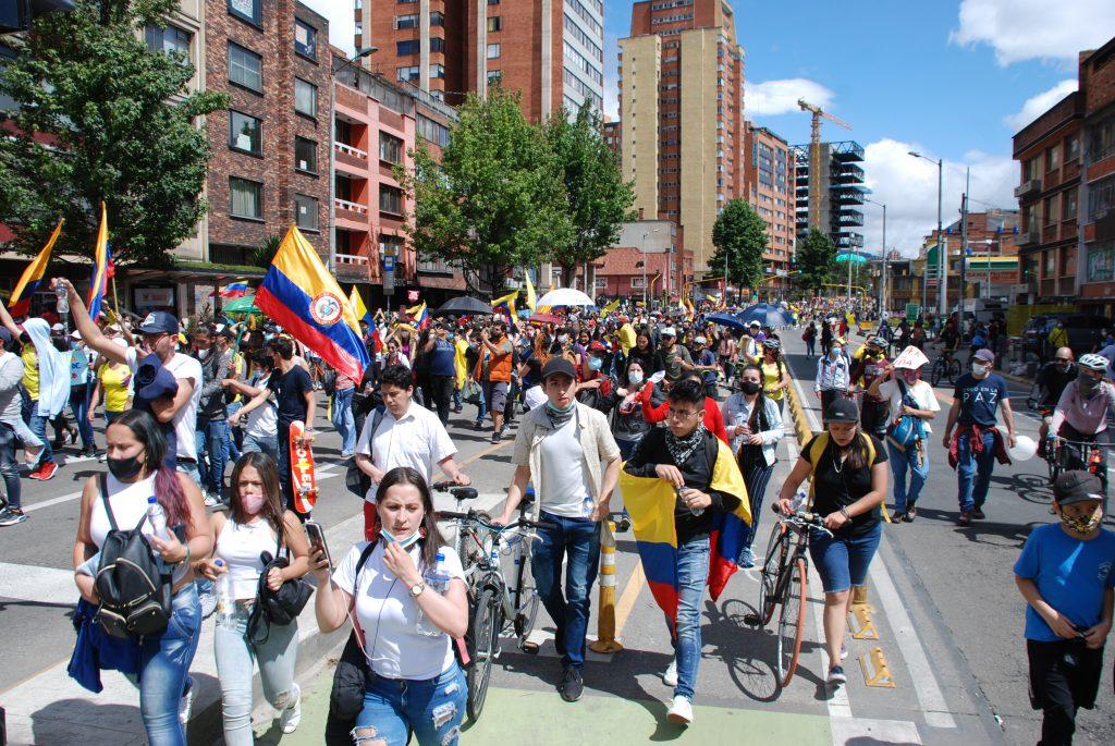 Man sieht eine Straße in einer Stadt in Kolumbien. Dort laufen viele Menschen mit kolumbianischen Flaggen in der Hand.