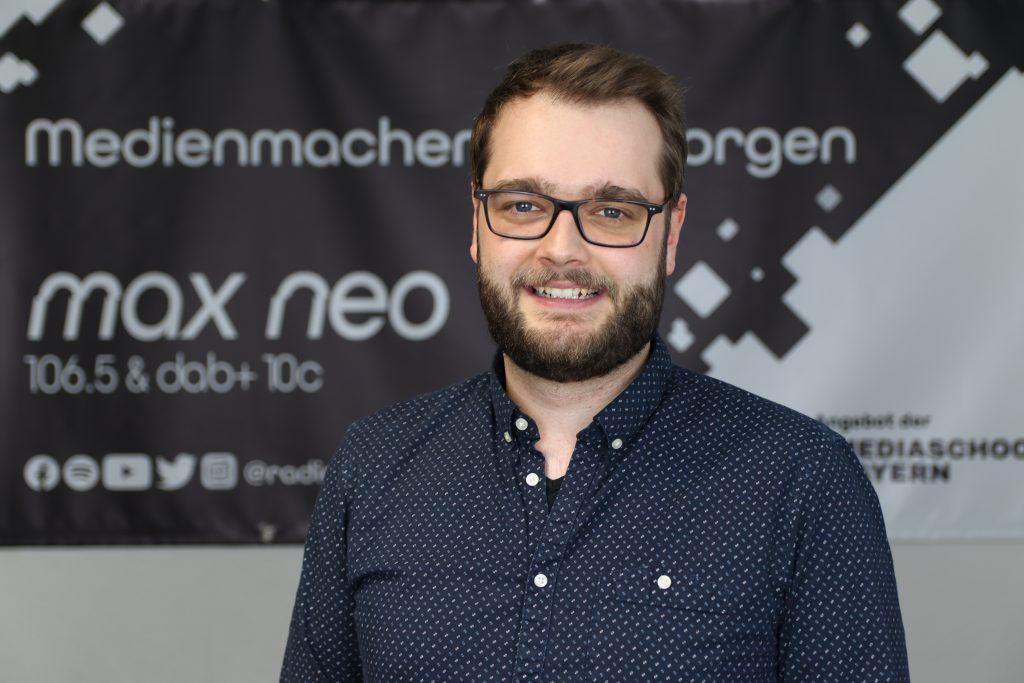 Maxi Auer steht vor dem max neo Banner.