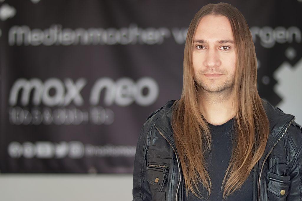 Matthias Engelhardt steht vor dem max neo Banner.