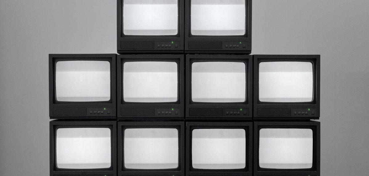 """Auf dem Albumcover """"Nowhere Generation"""" von Rise Against sieht man eine Pyramide aus alten Fernsehern vor einer grauen Wand."""