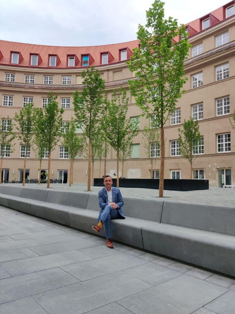 Auf den Bänken des Innenhofs des Tafelhof Palais sitzt ein Mann.