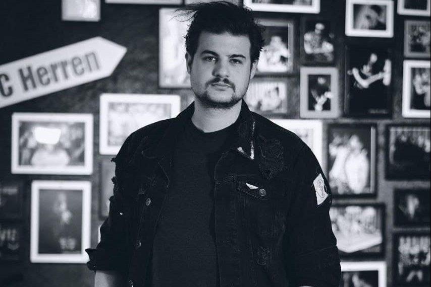 Das ist ein Schwarz-Weiß-Foto von Adrian Kontri, der vor einer Wand mit Bildern steht.