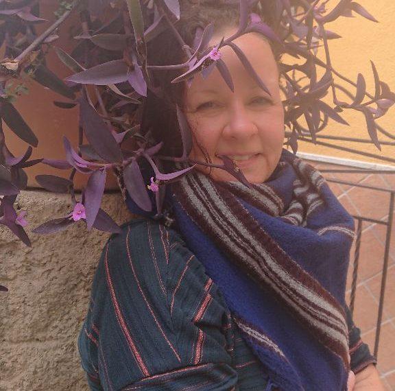 Andrea Heußinger steht vor einer Mauer. Über ihrem Kopf hängt eine Pflanze.