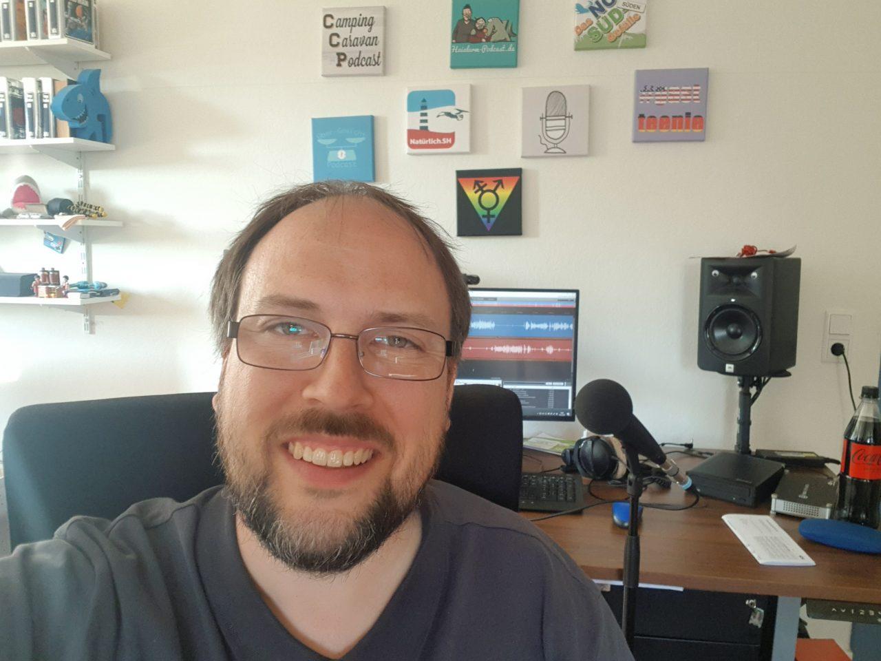 Jörn Schaar hat ein Selfie an seinem Schreibtisch gemacht. Im Hintergrund sieht man einen Computer, Mikrofon und Bilder an der Wand.