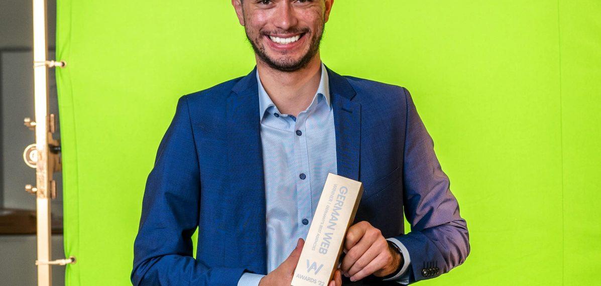 """Oliver Winkler steht vor einem Greenscreen mit einem """"German Web Award"""" in der Hand."""