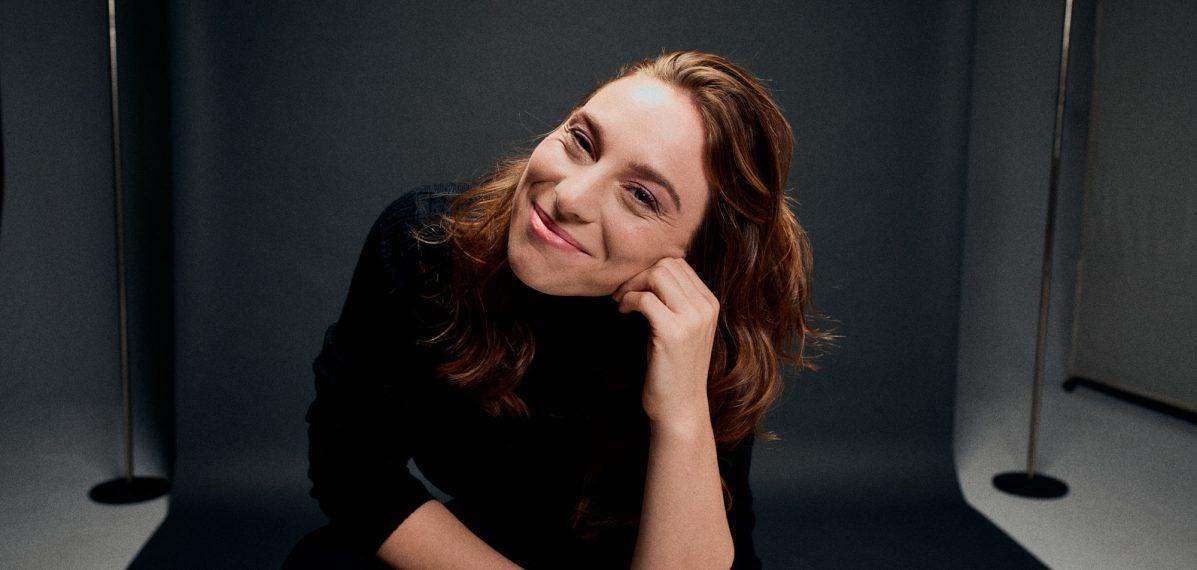 Luisa Filip sitzt in einem Fotostudio vor einer grauen Wand und lächelt in die Kamera.