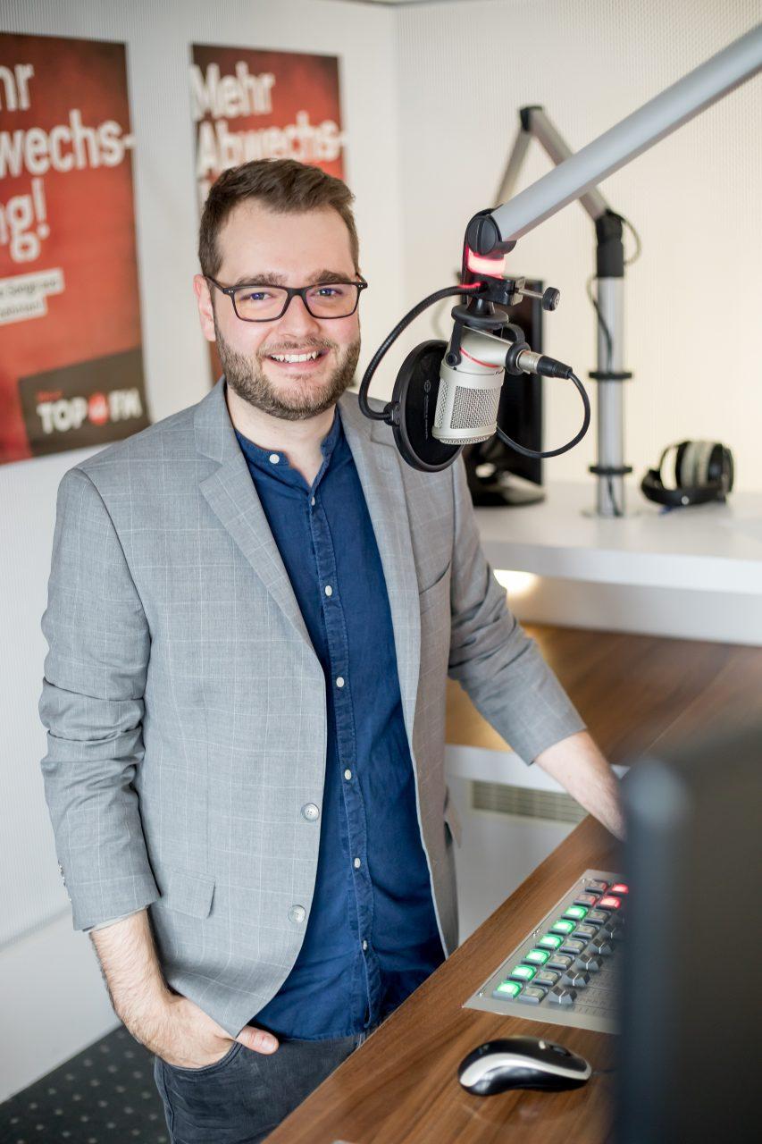 Maxi Auer steht im Studio von Radio TOP FM am Mischpult vor dem Mikrofon.