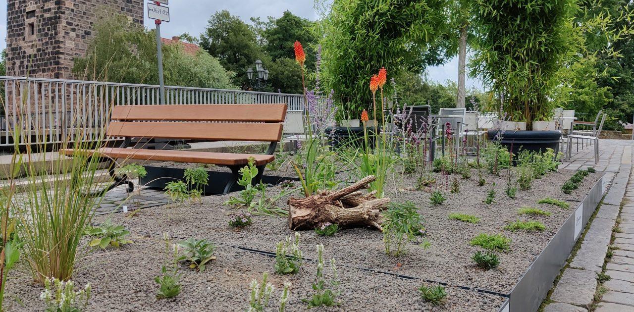 Im Vordergrund sind ein mobiles Blumenbeet und eine Sitzbank zu sehen. Im Hintergrund befinden sich Stühle und Tische von einem Cafe sowie eine Brücke.