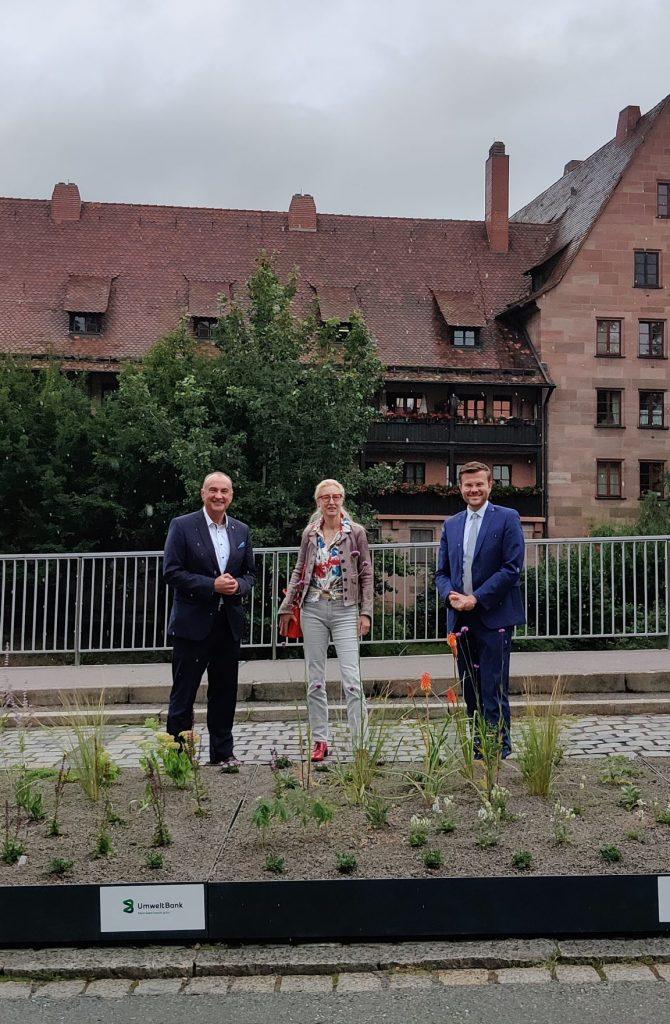 Goran Basic von der Umweltbank, Daniela Bock vom Verein Grünclusiv e.V. und Nürnbergs Oberbürgermeister Marcus König (von links nach rechts) stehen hinter dem mobilen Grün am Unteren Bergauerplatz.