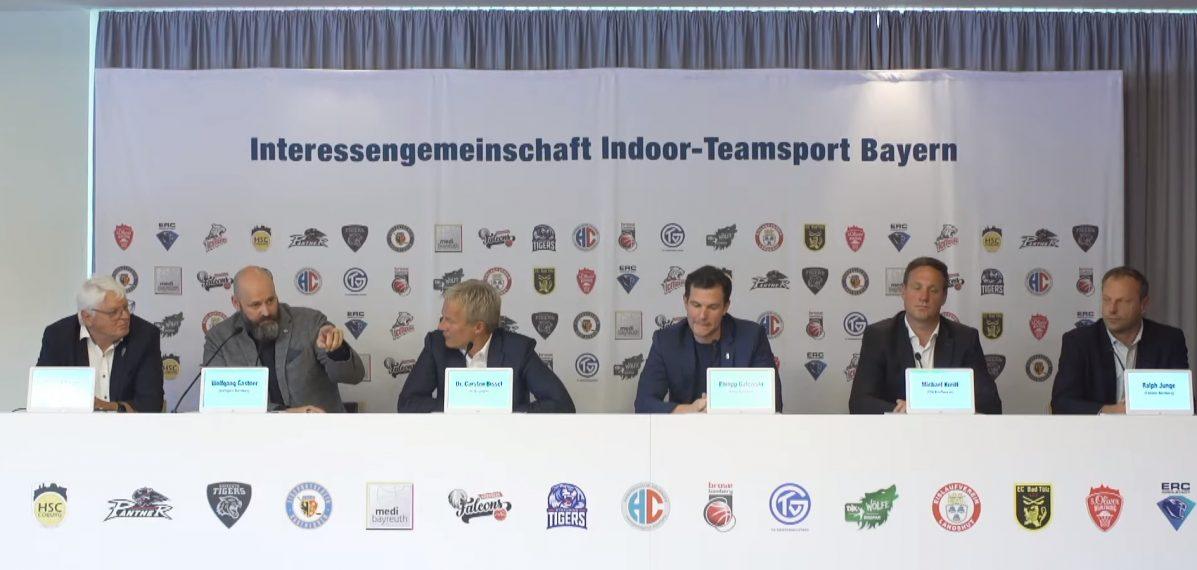 Auf dem Foto sieht man sechs Vertreter der Interessengemeinschaft Indoor-Teamsport Bayern bei einer Pressekonferenz.