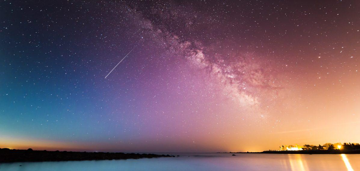 Auf dem Foto ist das Meer zu sehen. Darüber sieht man den Nachthimmel mit einer Vielzahl von Sternen und einer Sternschnuppe. Im Hintergrund sind Lichter einer Stadt zu sehen.
