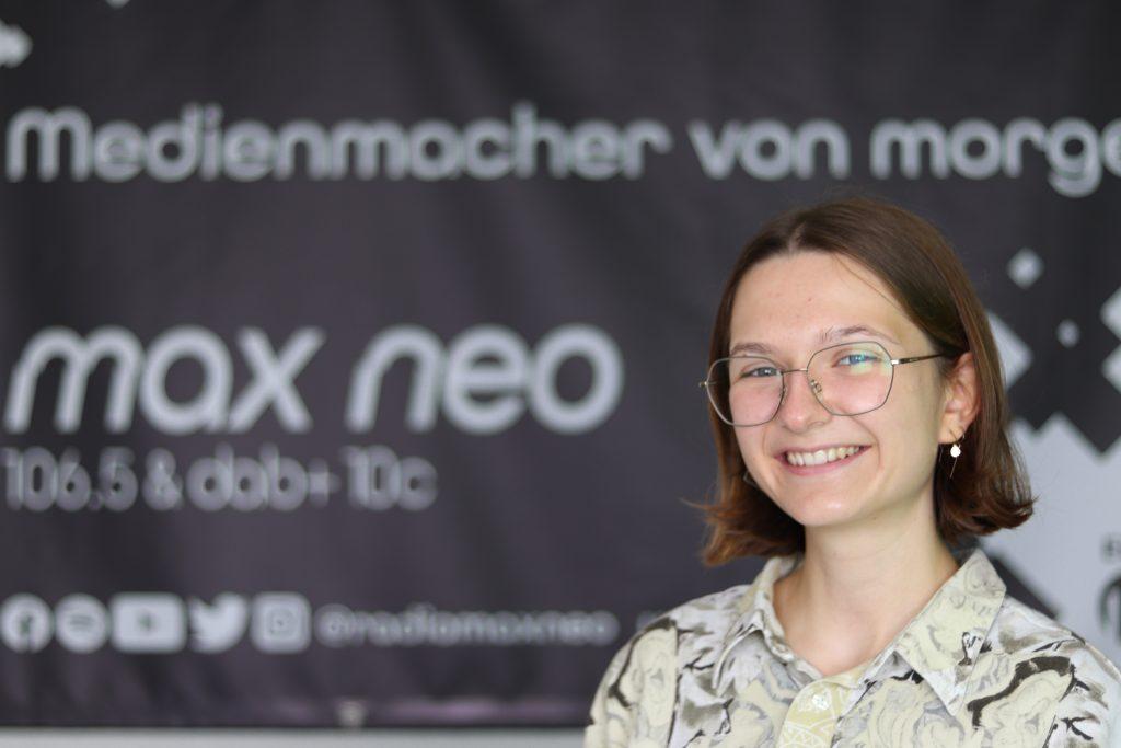 Praktikantin Elena Geigl steht vor dem max neo Banner. Sie ist im Porträt zu sehen.