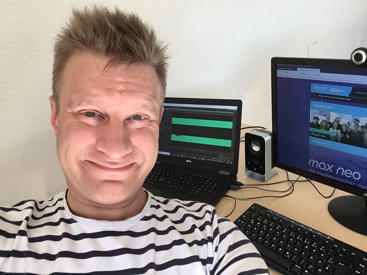 Holger Müller sitzt an seinem Schreibtisch im Home Office. Im Hintergrund des Selfies sind ein PC mit Tastatur und ein Laptop zu sehen.