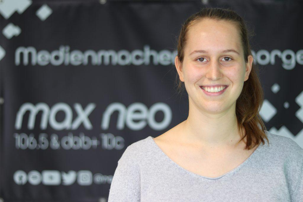 Luna Neuwerth ist im Porträt vor dem max neo-Banner zu sehen.