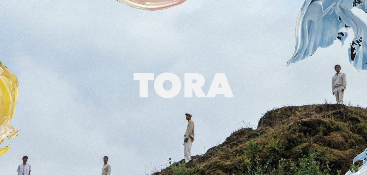 """Das Albumcover """"A Force Majeure"""" von Tora zeigt die Bandmitglieder, wie sie auf einem grasbewachsenen Hügel stehen. In den Ecken des Bildes sind verschiedene Pinselstriche mit Farbe zu sehen."""