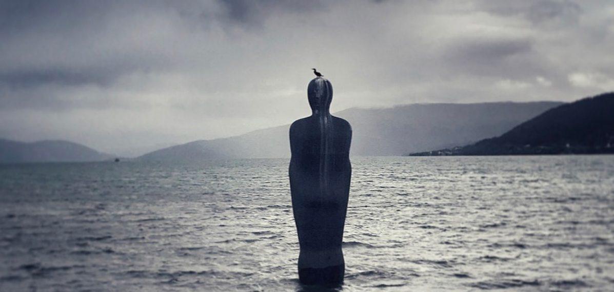 """Das Albumcover """"Falling From Fame"""" von tAKiDA zeigt eine Statue im Meer. Auf dem Kopf der Statue sitzt ein Vogel. Im Hintergrund sieht man Berge und graue Wolken am Himmel."""