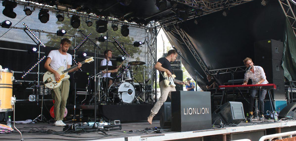Das Foto zeigt LionLion bei ihrem Auftritt 2018 auf dem Weinturm Open Air in Bad Windsheim. Die vier Jungs spielen gerade einen Song auf der Bühne.