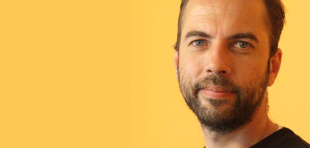 Das Foto zeigt Matti Kunstek im Porträt. Er steht vor einer gelben Wand.