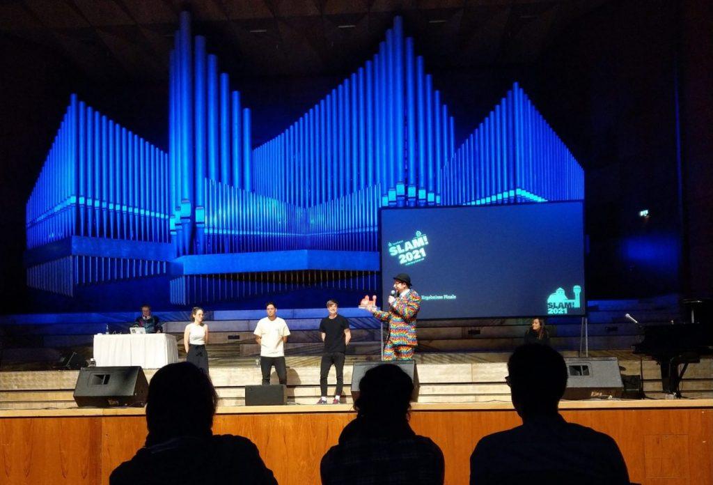 Man sieht die Bühne der Meistersingerhalle, auf der die drei Finalisten und der Moderator mit der Trophäe stehen. Im Hintergrund ist die blau beleuchtete Orgel zu sehen.