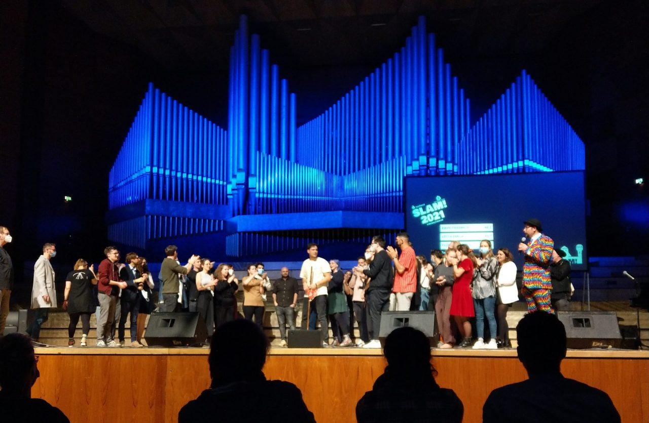 Auf der Bühne stehen einige Poetry Slammer*innen, die den Gewinner David Friedrich beklatschen.