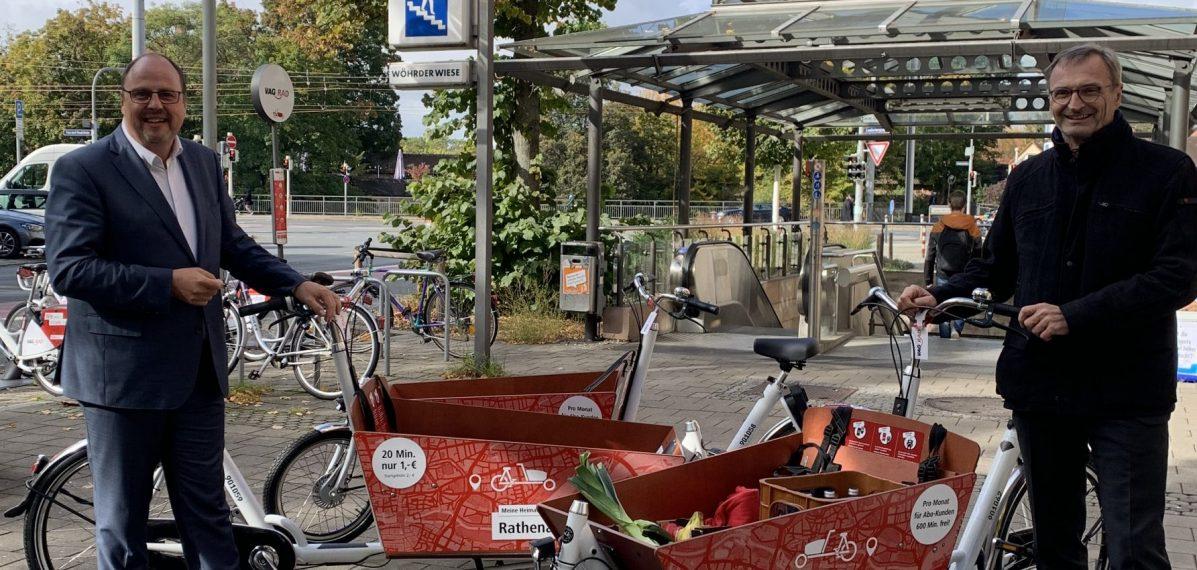 Im Hintergrund ist die U-Bahnstation Wöhrder Wiese zu sehen. Davor stehen Christian Vogel und Josef Hasler. Dazwischen stehen drei Lastenräder der VAG Nürnberg.