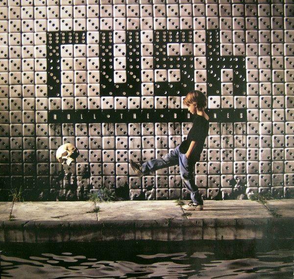 """Das Albumcover """"Roll The Bones"""" von Rush zeigt eine Wand aus weißen und schwarzen Würfeln. Die schwarzen Würfeln bilden das Wort """"Rush"""". Vor der Wand steht ein Junge, der einen Totenkopf mit dem Fuß wegkickt."""