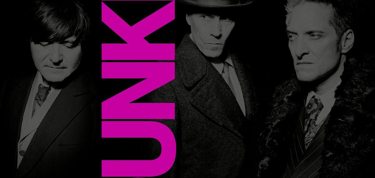 """Das Albumcover """"Dunkel"""" von Die Ärzte ist schwarz-weiß. Es zeigt die drei Bandmitglieder im Porträt. Vertikal steht in fetten, pinken Buchstaben """"Dunkel""""."""