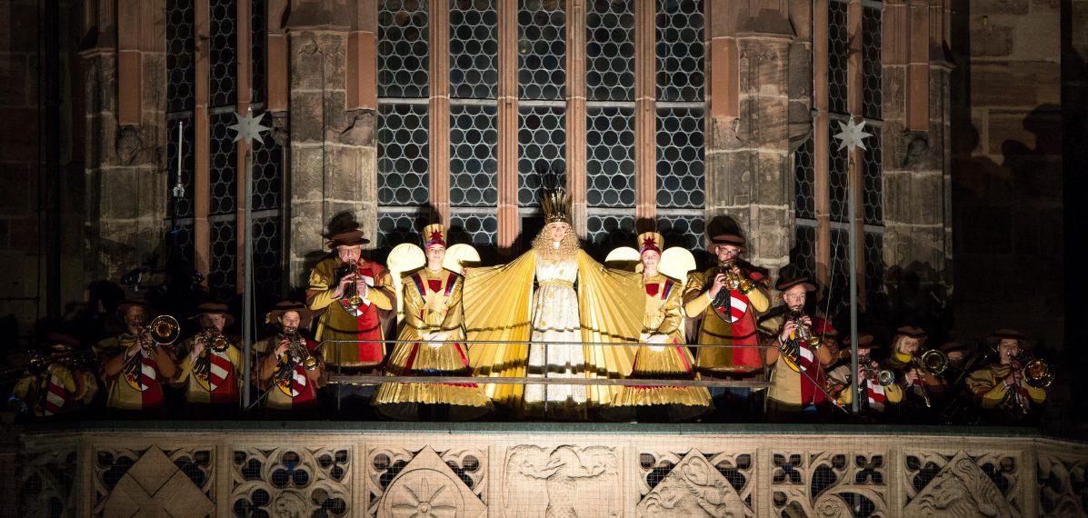 Auf dem Foto sieht man die Empore der Frauenkirche. Dort stehen mehrere Menschen. In der Mitte steht Benigna Munsi als Nürnberger Christkind und sagt den Prolog auf.