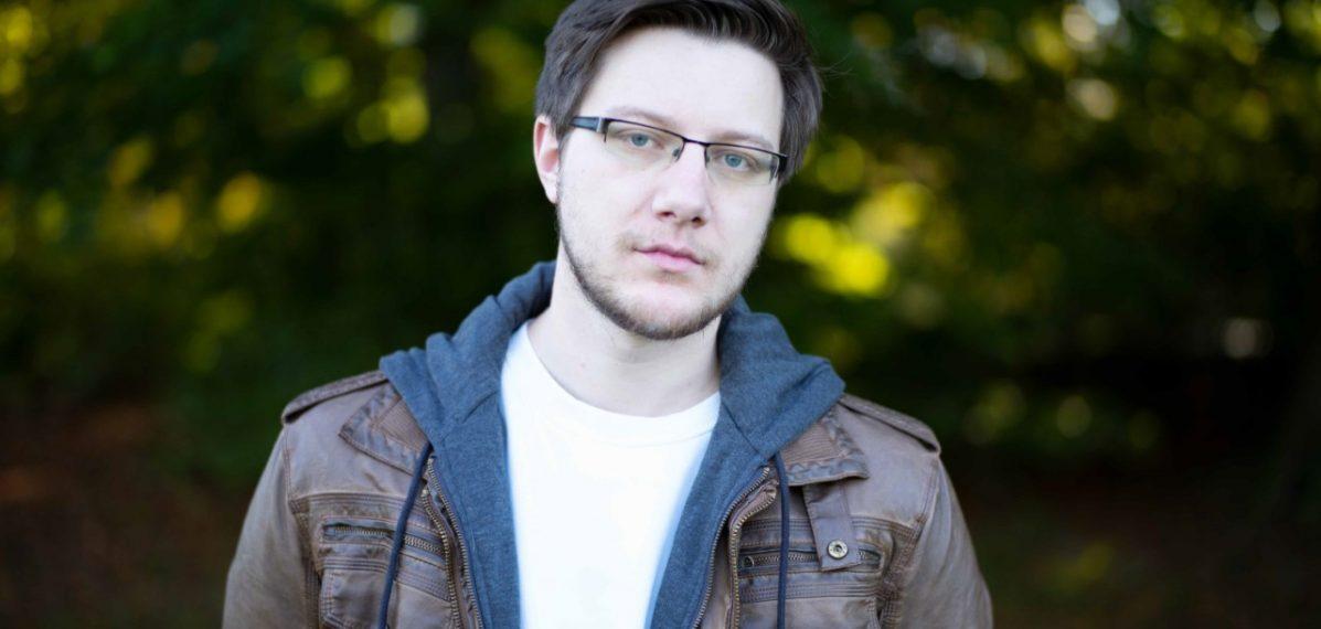Yannik Sellmann steht vor Bäumen und ist im Porträt zu sehen.